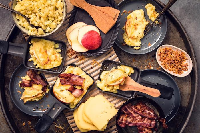 vier kleine schwarze pfännchen für raclette mit geschmolzenem käse geschnittene äpfel die raclette zutaten