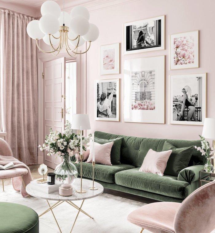 wandfarbe rosa grünes sofa mit pinken und grünen kissen runder tisch vase mit blumen wanddekoration wohnzimmer schwarz weiße fotos moderne inneneinrichtung inspiration