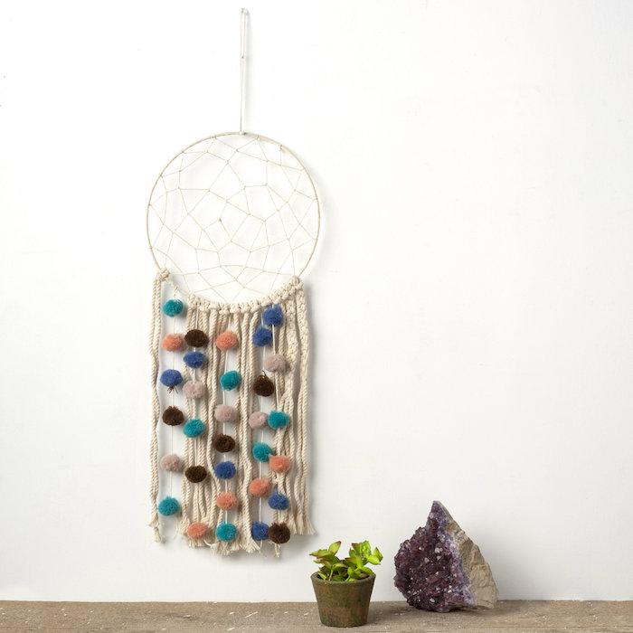wandhänger makramee wanddeko diy aus baumwolle dekorative bunte bällchen vase mit kleiner grüner kaktee quartz stein lila minimalistische einrichtung