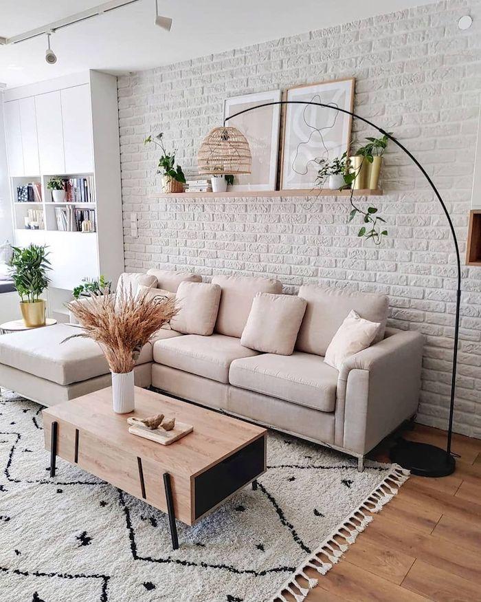weiße backsteinmauer cremefarbenes ecksofa holzboden gemütliches wohnzimmer modern einrichten stylischer kaffeetisch aus holz modische inneneinrichtung inspo
