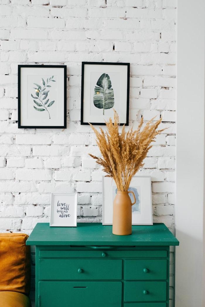 weiße backsteinwand wanddeko bilder tropische muster kleine grüne kommode skandinavische einrichtung inspiration ockerfarbene vase mit pampasgras bild mit inspirierendem zitat