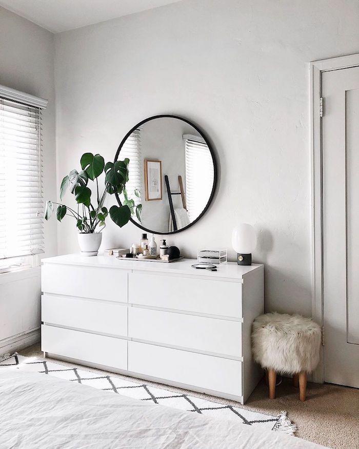 weiße kommode skandinavische einrichtung schlafzimmer runder spiegel mit schwarzem rahmen deko grüne pflanze hocker skandinavisch flauschige polsterung zimmer weiße ästhetik