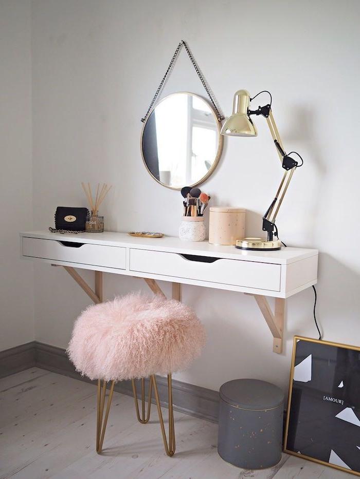 weißer schminktisch zwei schubladen mittelgroßer runder spiegel pinker dreibeiniger goldener hocker skandinavisch flauschige polsterung gruaer mülleimer unaufgehängtes bild