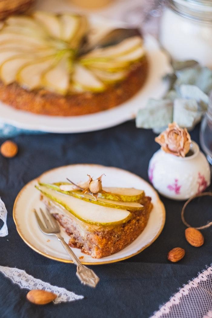 weißer teller mit einem kuchen mit frischer birne gabel eine blaue decke ideen für kuchen mit wenig zutaten