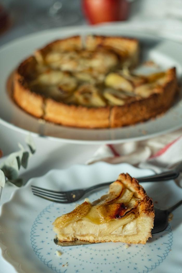 weißer teller mit gabel und einem kuchen mit frischen äpfeln und zimt rezepte für kuchen mit äpfeln