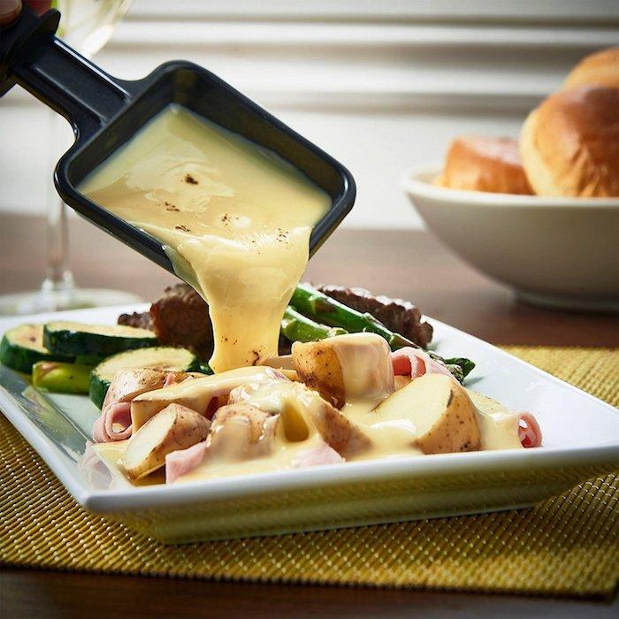 weißer teller mit gemüse und geschmolzenem käse raclette zutaten brot ein schwarzes pfännchen mit käse für raclette