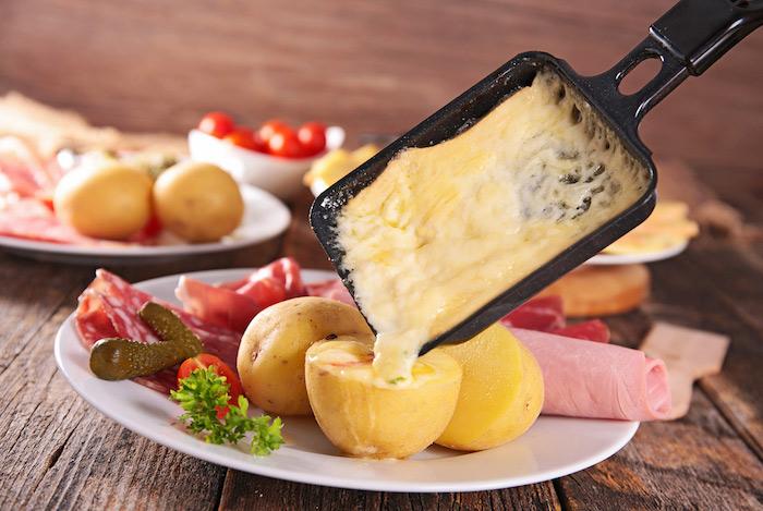 weißer teller mit kartoffeln und grunken schinken tisch aus holz ein schwarzes pfännachen mit geschmolzenem käse für raclette