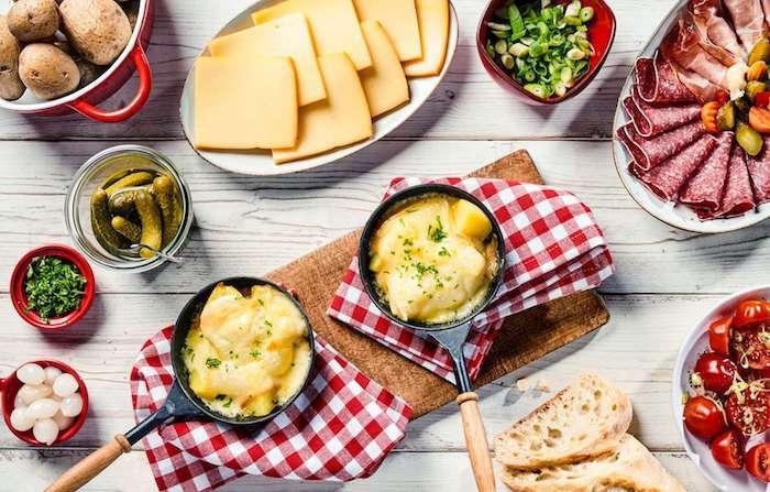 weißer tisch aus holz raclette zutaten ideen raclette käse gurken schinken und salami pfanne mit geschmolzenem käse
