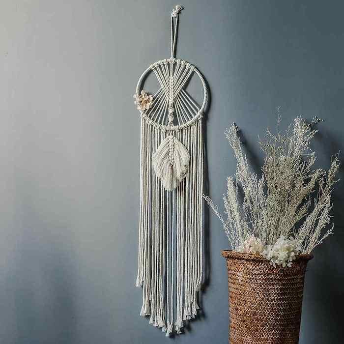 weidenkorb mit deko blumen langer boho traumfänger minimalistisches design grau blaue wandfarbe inneneinrichtung inspiration