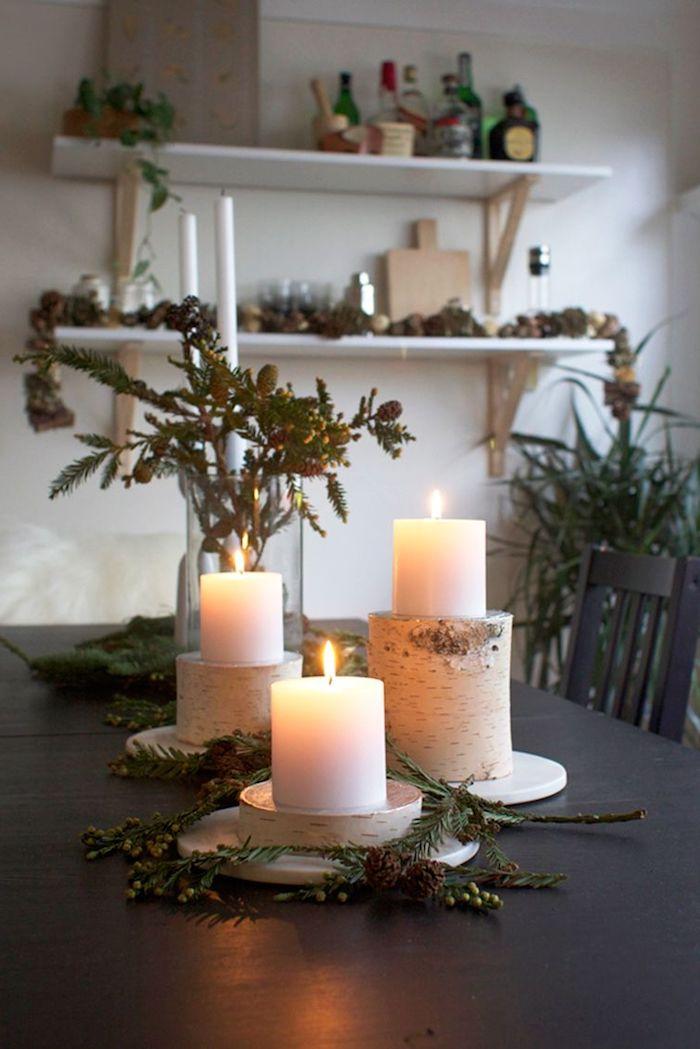 weihnachten dekoration inspiration holzstamm deko kerzenhalter aus birkenholz große weiße kerzen grüne tannenzweige wohnzimmer deko festlich großer esstisch offene regale