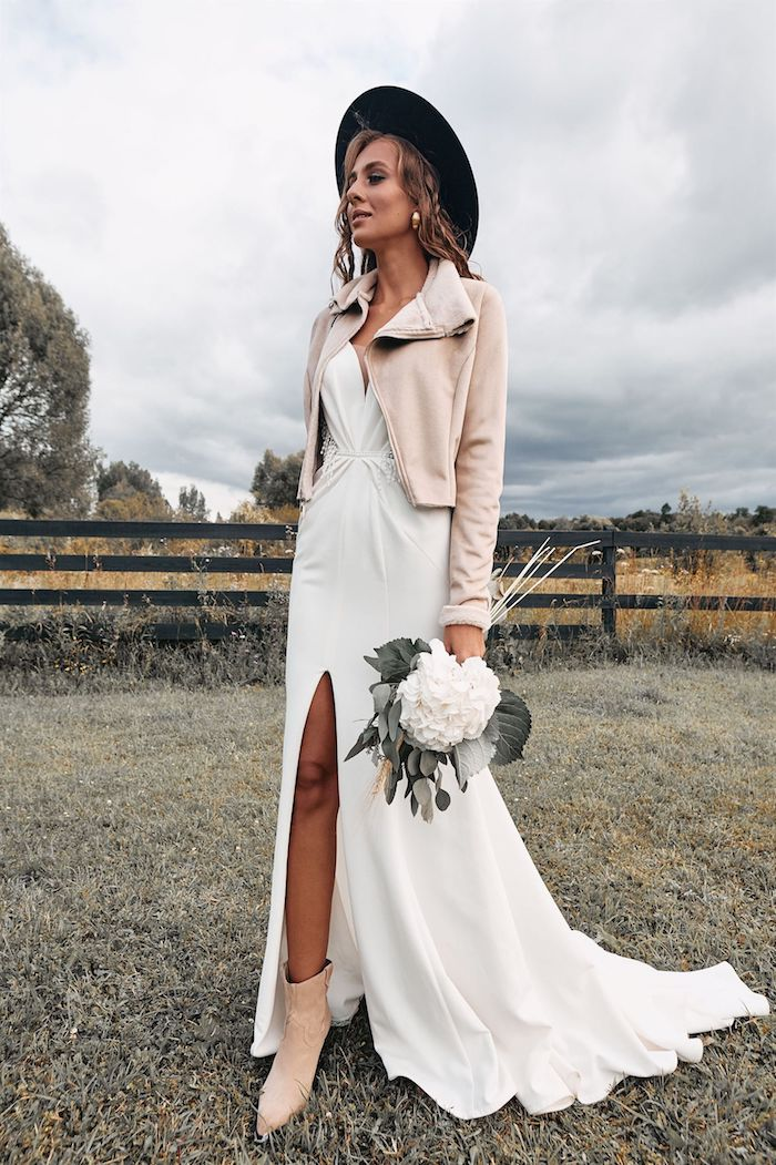 winter brautjacke beige farbe kunstpelz jacke langes weißes klied mit schlitz accessoires schwarzer hut boho brautkleid schöner strauß mit weißer blume hippie style