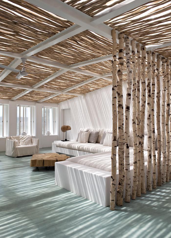wohnzimmer einrichtung birkenstamm raumteiler großes ecksofa weiß haus am strand inneneinrichtung grüner bodenbelag kaffeetisch aus holz moderne ausstattung