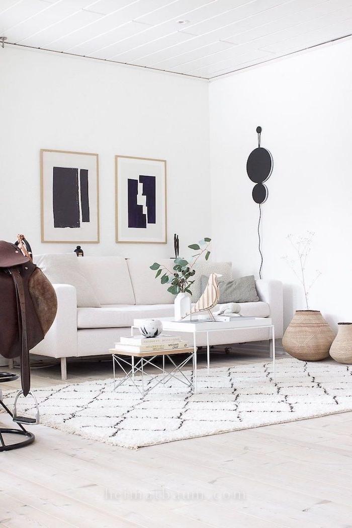 wohnzimmer modern einrichten abstrakte schwarze gemälde eleganter weißer couch skandinavische deko figuren vogel vase mit grünen zweigen weißer teppich