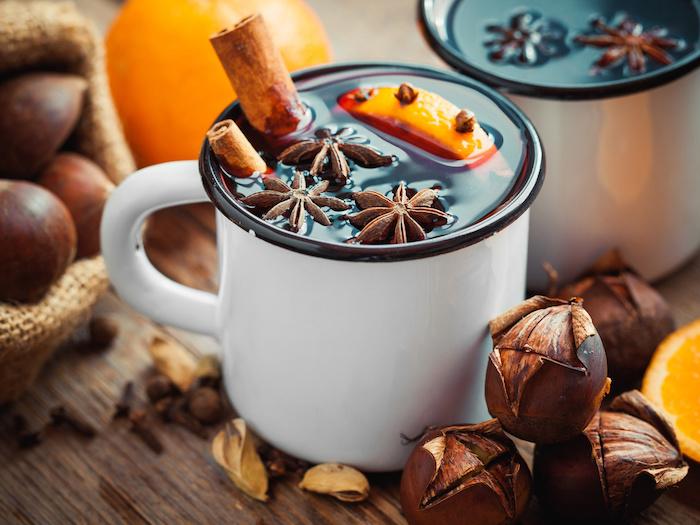 zubereitung esskastanien tee aus maronen mit zimt orangen und vanille weißer necher mit gebackenen maronen