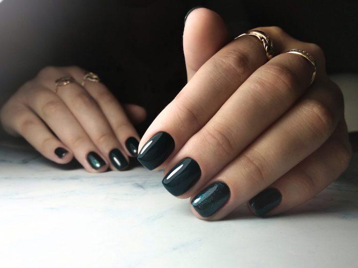zwei hände mit einem dunkelblauen nagellack und mit großen goldenen ringen