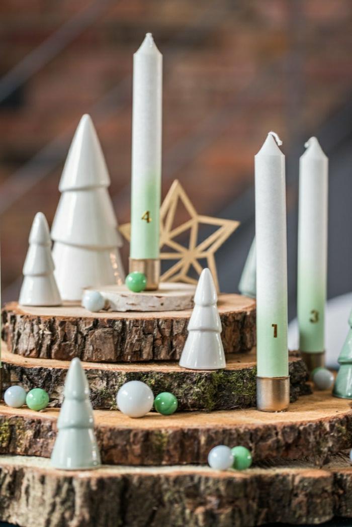 adventskranz baumscheiben vier kerzen weiße tannenbäume keramik kleine kugeln weiß grün