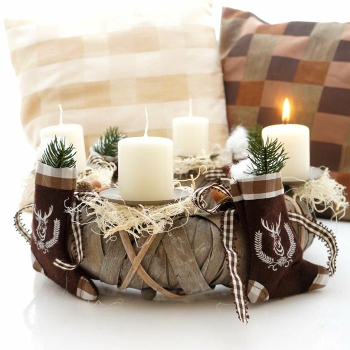 adventskranz holzscheibe basteln anleitung kerzen auf kerzenteller kleine socken tannenzweig zwei kissen weiß braun