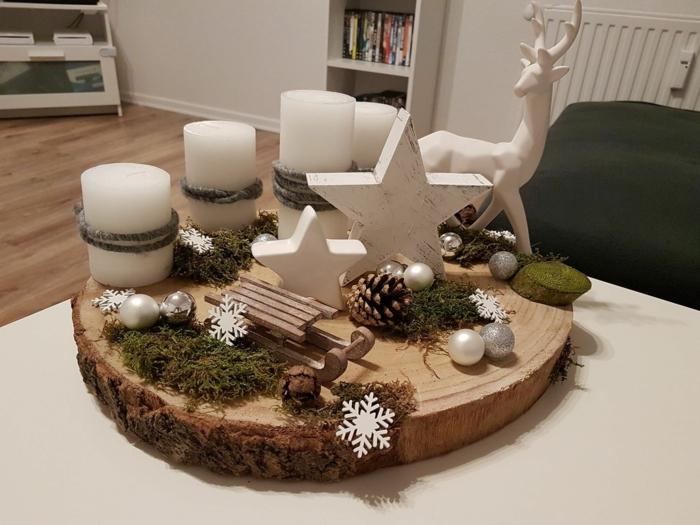 adventskranz selber machen baumscheibe vier weiße kerzen große hirsche keramik holz schlitten kleine kugeln sterne flocken moos