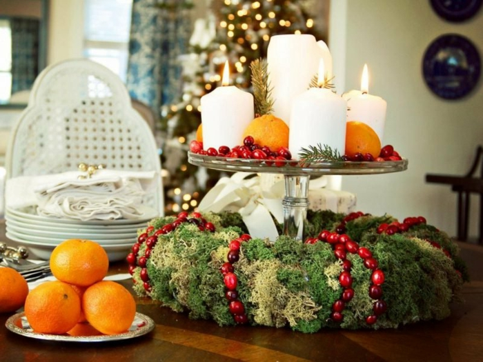 adventskranz selber machen holzscheibe moos rote beeren vier kerzen auf teller orangen tisch