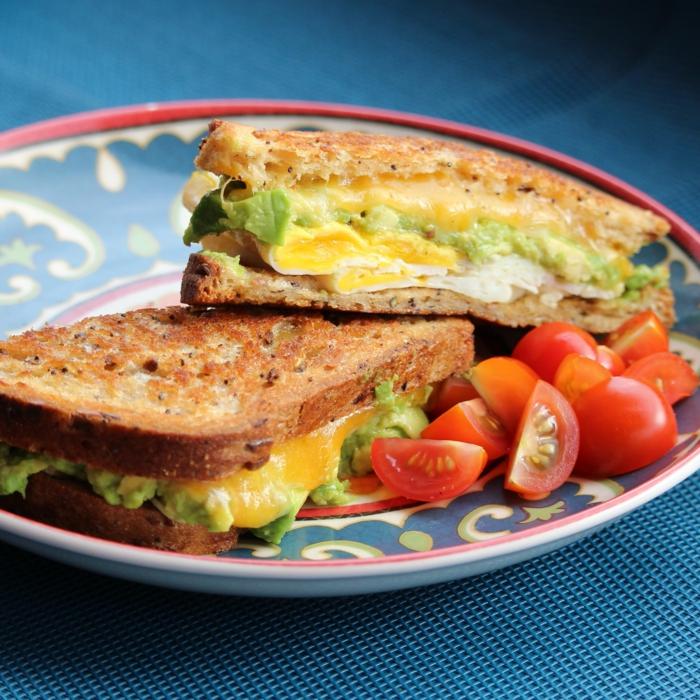 blauer teller mit zwei stullen mit senf und salat und kleinen roten tomaten eine avocadocreme