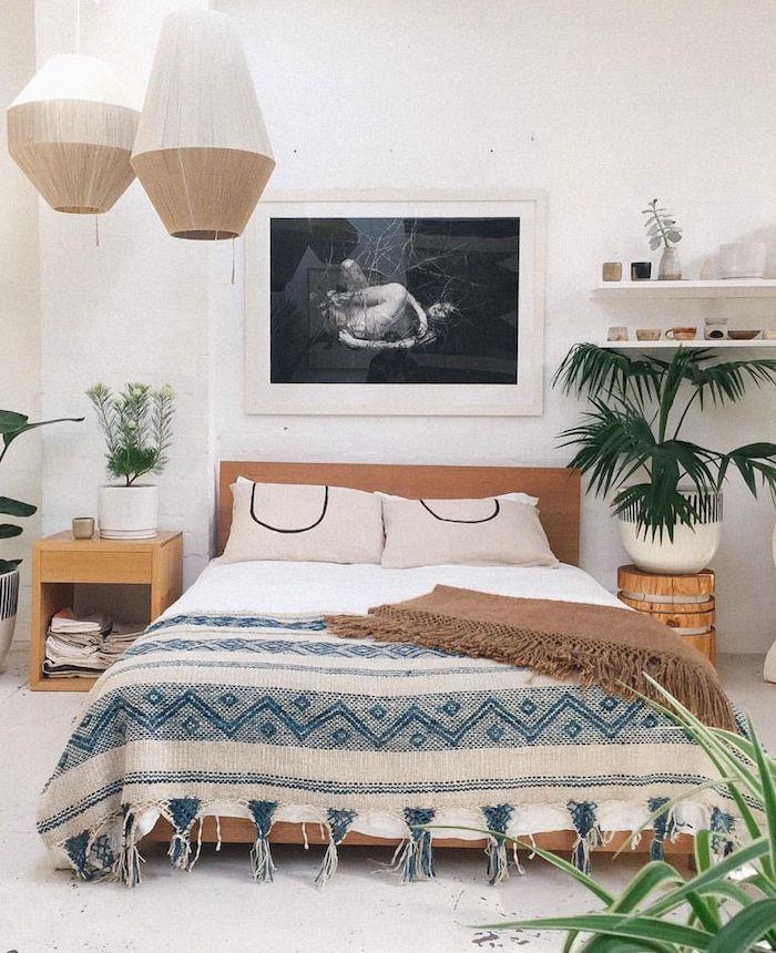 boho deko schlafzimmer bett boho bett blaue decke holz pflanzen wandfoto schwarz weiße rahmen