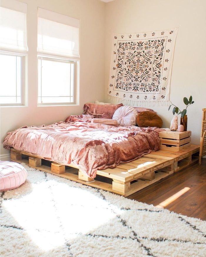 boho deko schlafzimmer großes holzbett auf dem boden boho bettwäsche rosa wanddeko tuch boho motive