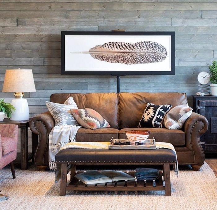 boho deko style wohnzimmer holz wand grau print feder schwarze rahmen braunsofa tisch latterne