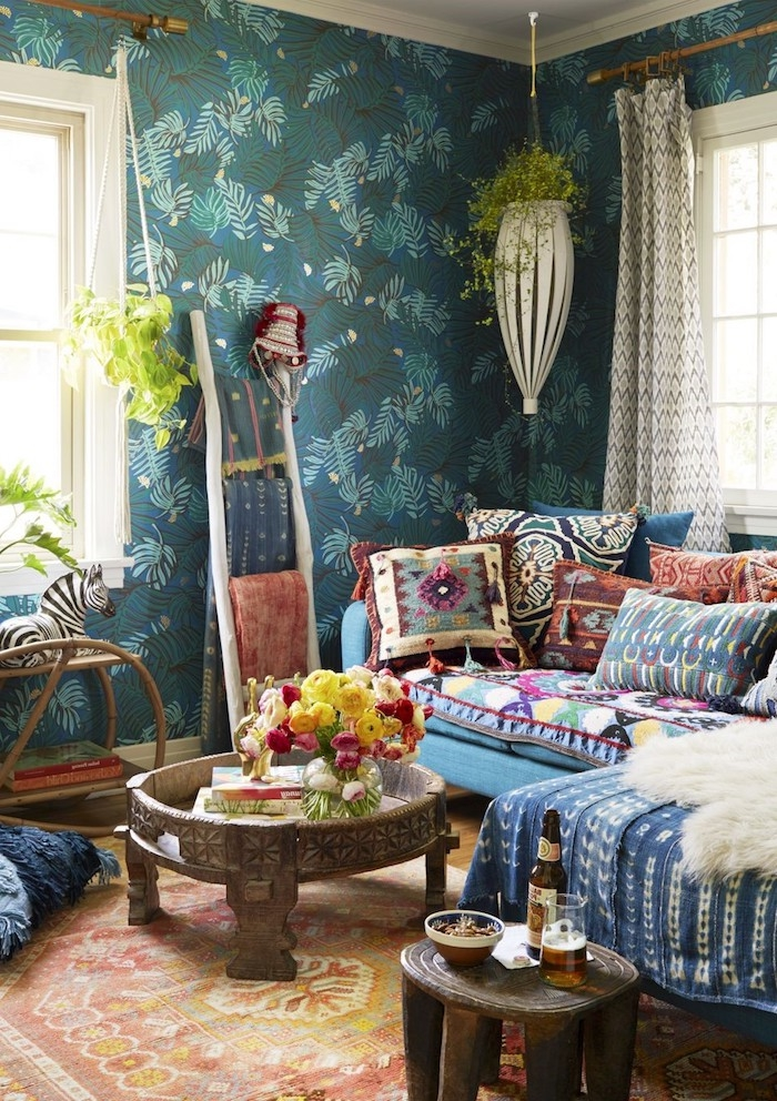 boho style einrichtung wohnzimmer turkisblaue wände blaues sofa bunte kissen holztisch pflanzen hängen