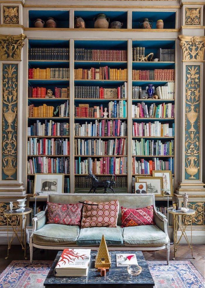 boho style wohnen wohnzimmer große bibliothek aus holz gold blau eingebaut sofa hellgrün rote kissen tisch