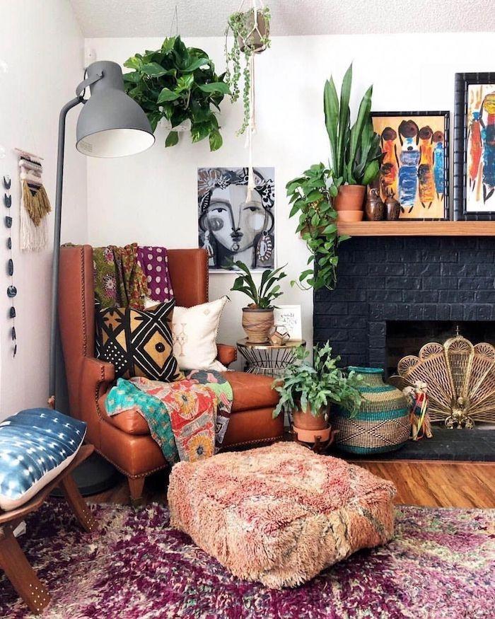 boho style wohnen wohnzimmer ledersessel braun kissen wanddeko bilder frau pflanzen rot teppich boden