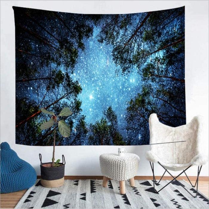 boho wohnzimmer wandtuch blau wald himmel auf weißer wand weiße stuhl und tisch pflanze sitzsack