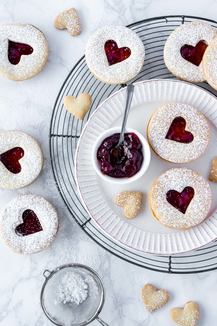 chefkoch weihnachtsplätzchen backen runde kekse in herzform kleine weiße schüssel mit marmelade sieb mit puderzucker