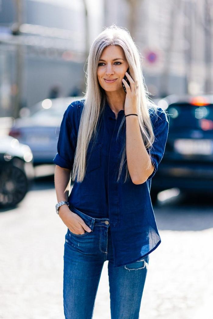 die designerin sarah harris eine frau mit langen grauen haare und mit jeans und einem smartphone