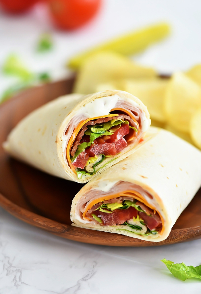 ein brauner teller mit wraps mit avocado und tomaten und kleinen geschittenen zitronen