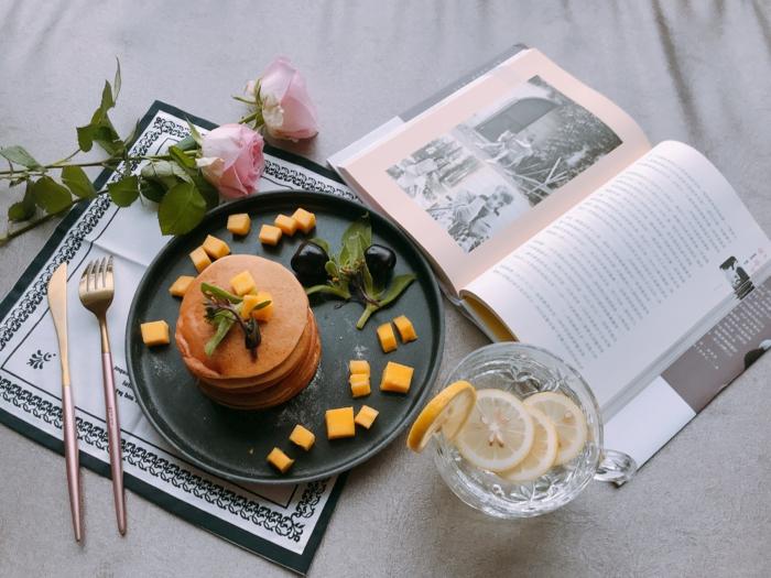 ein buch une geschnittene gelbe zitronen zwei rosen und kleine pfannkuchen