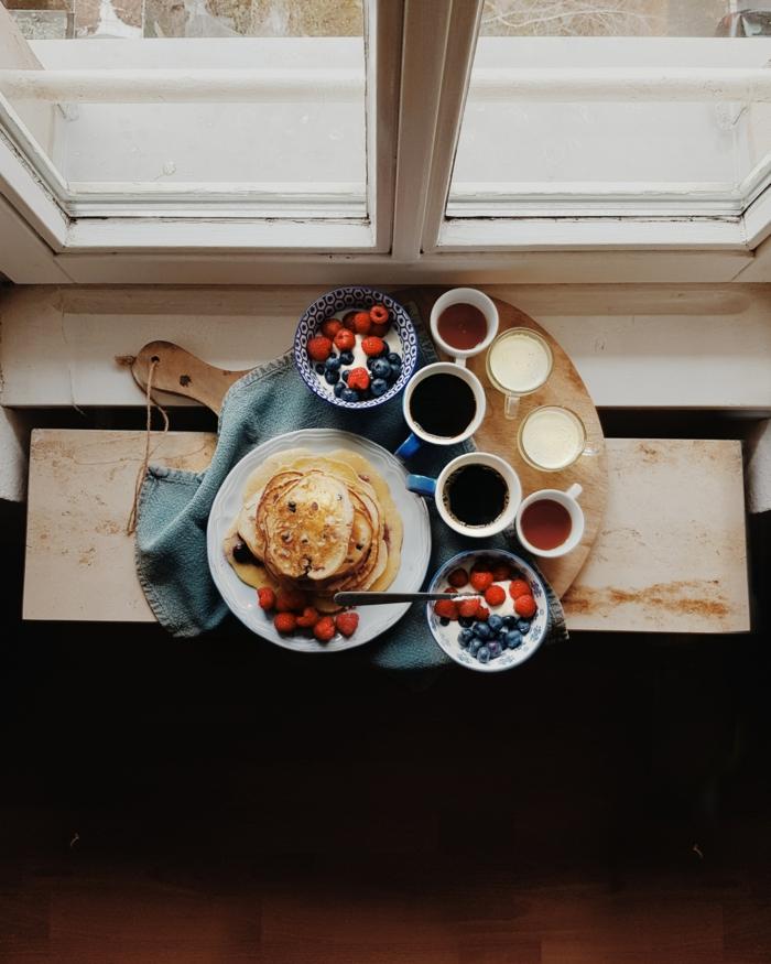 ein fenster und eein holzbrett mit weißem teller mit pfannkuchen blaubeeren und himbeeren