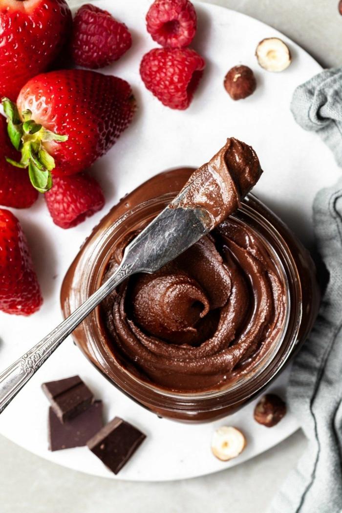 ein messer und schokolade ein veganes nutella selber machen teller mit roten erdbeeren