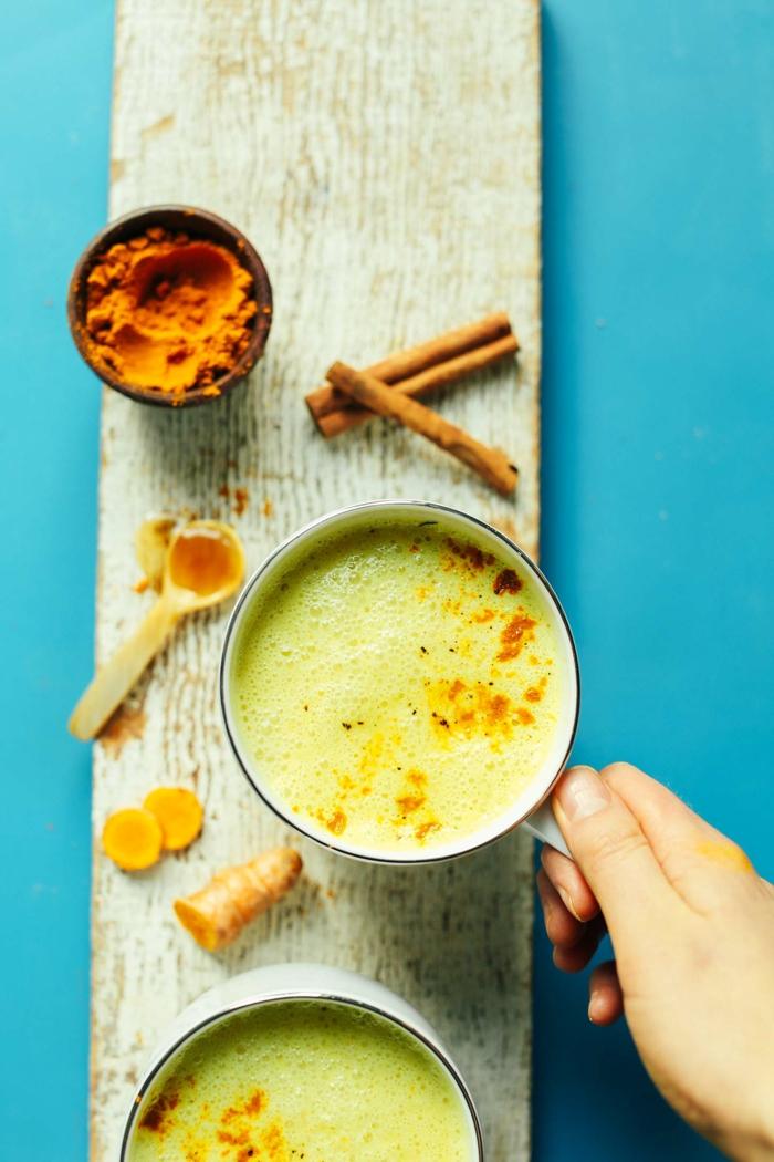 eine hand mit tasse mit goldener milch dezutaten goldene milch kurkuma zimt und ingwer