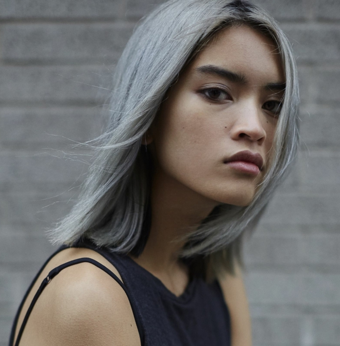 eine junge frau mit grauen haaren und dunkelblauem kleid und natürlichem make up