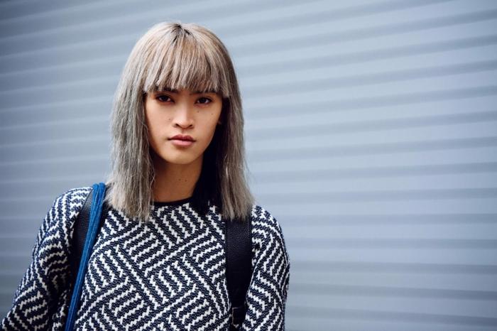 eine junge frau mit grauen haaren und einem schwarz weißen pullover graue haare pflegen