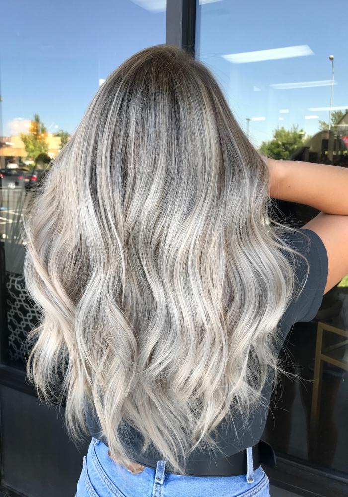 fenster und ein blauer himmel eine fra mit einer frisur mit langen grauen haaren und mit jeans