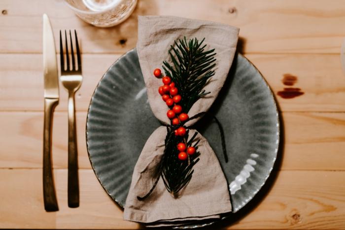 festliche dekoration weihnachten servietten falten einfach tannenzweige dekoration grauer teller minimalistische tischdeko
