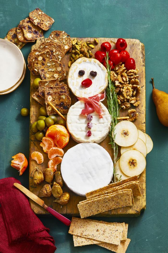 festliche vorspeisengutvorzubereiten brett brie käse kräckers walnüsse schneemann