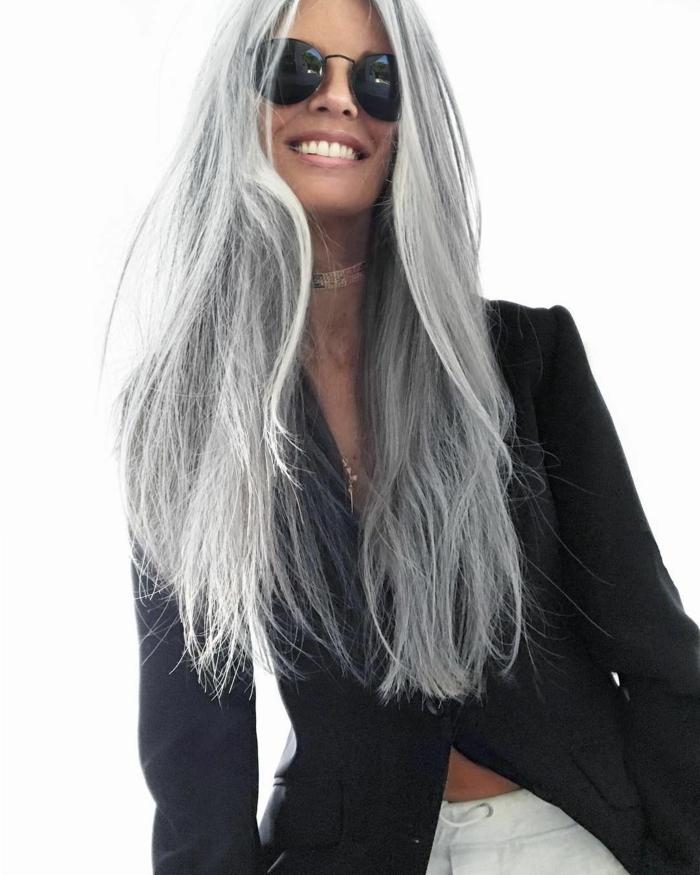 frau mit brille und langen grauen haare und einem schwarzen sakko tipps für pflege von grauen haaren