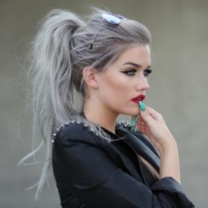 frau mit schwarzem sakko einem grauen haar und grünem nagellack graue haare richig pflegen tipps