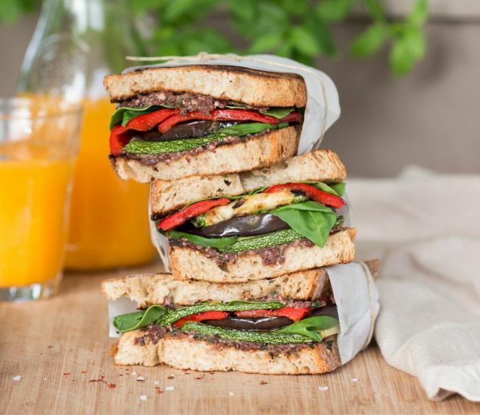 glas mit orangensaft ein brett aus holz drei stullen mit salat und roten omaten gesundes abendessen ideen