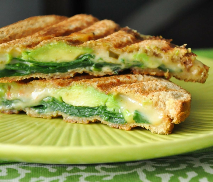 grüner teller mit zwei stullen mit einer grünen avocadocreme und mit gurken rezept f rgesundes abendessen