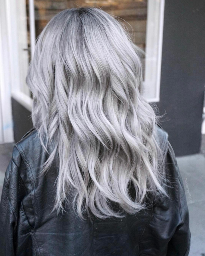junge frau mit einer schwarzen ledderjacke eine frisur mit langen grauen haaren