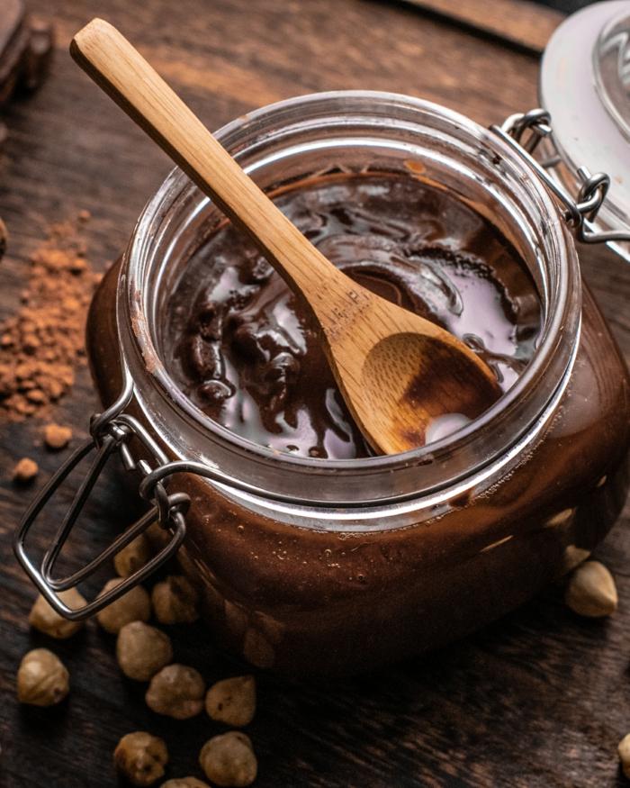 kakaopulver und haselnüsse auf tisch aus holz ein glas mit einer nutella alternative vegan