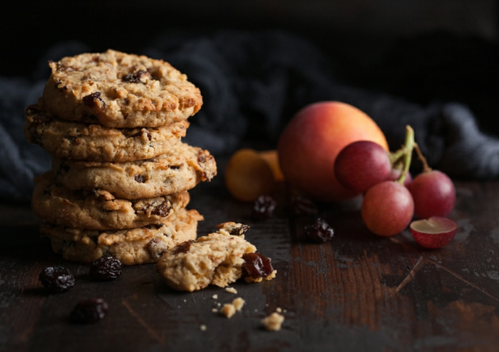 homemade organic oatmeal cookies with raisins and apricots on dark wooden background with apricot and grapes.
